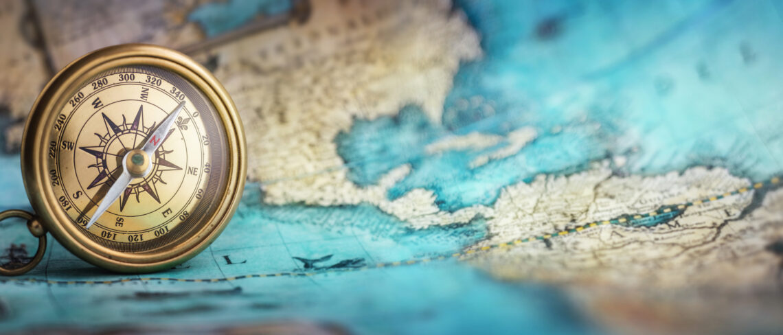 Magnetic old compass on world map.Travel, geography, navigation, tourism and exploration concept background